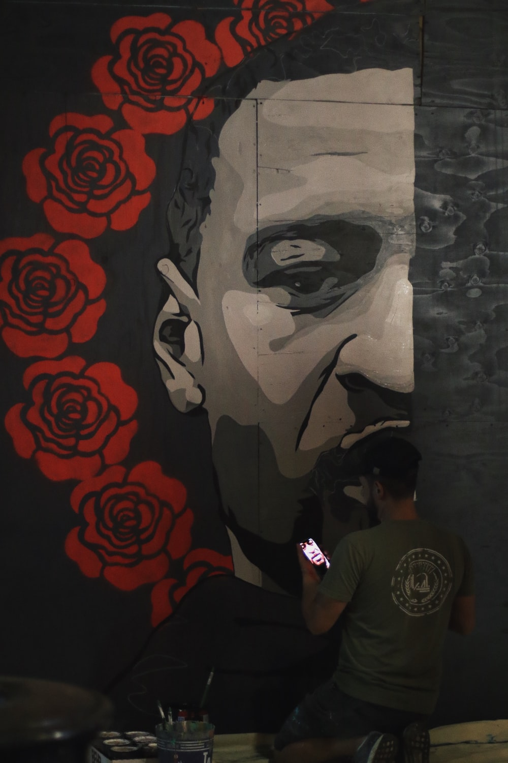 man in black crew neck t-shirt standing beside wall with graffiti