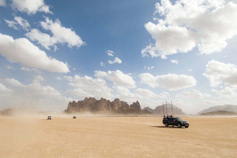 black car on brown sand under blue sky during daytime