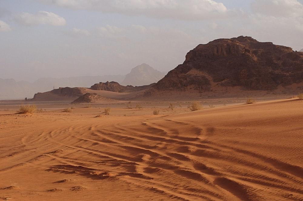 brown sand field near brown mountain under white sky during daytime