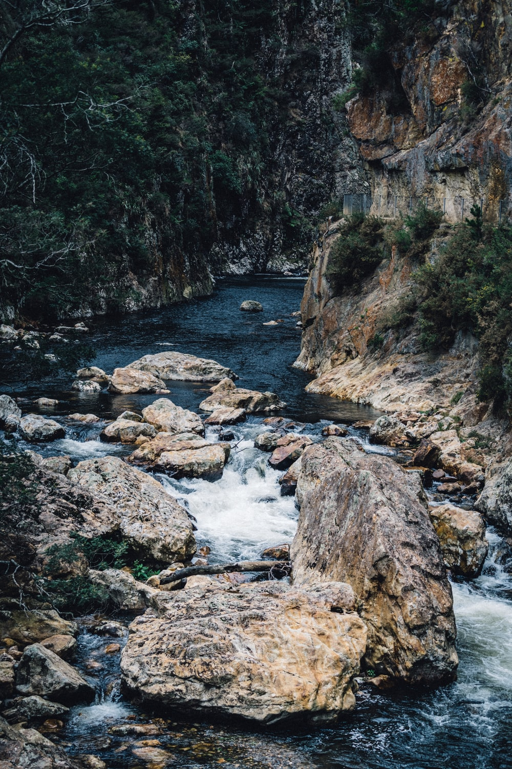 river in between rocky mountain during daytime