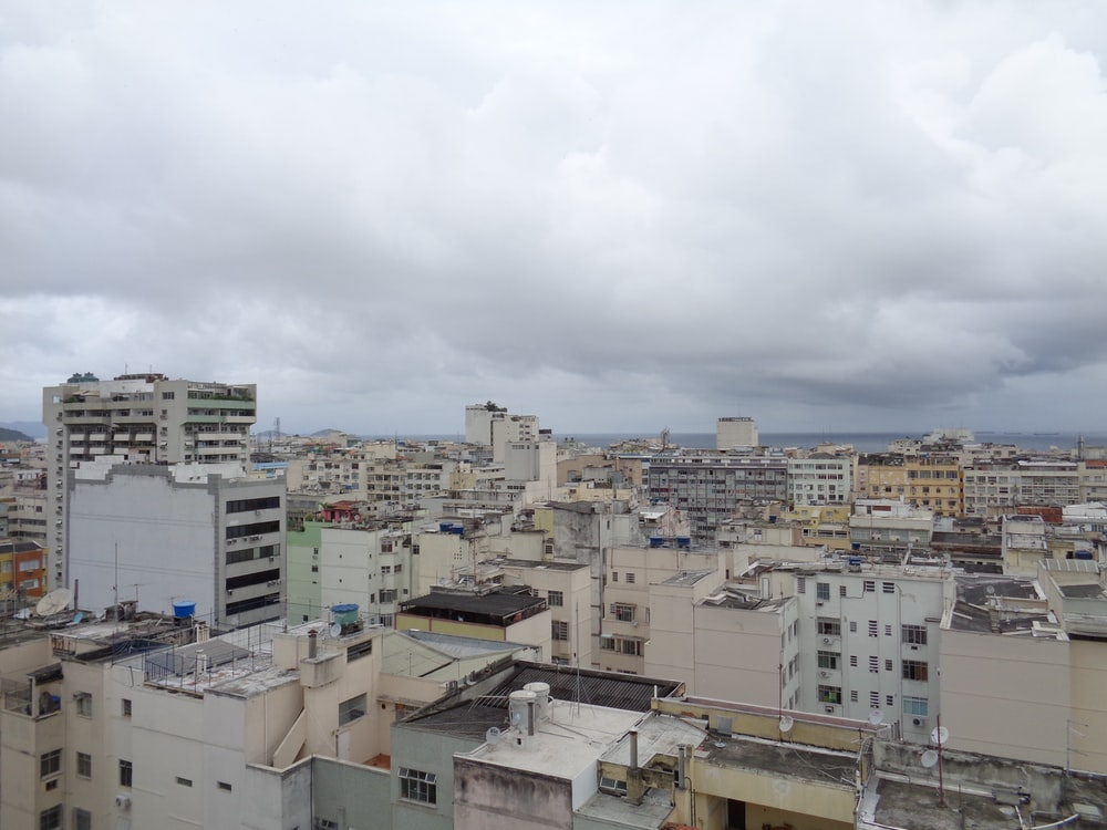 white and brown concrete buildings under white clouds during daytime