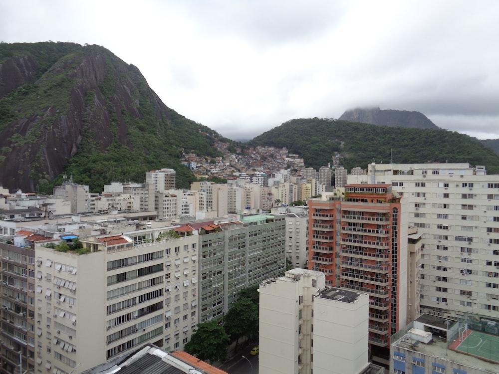 white concrete building near green mountain during daytime