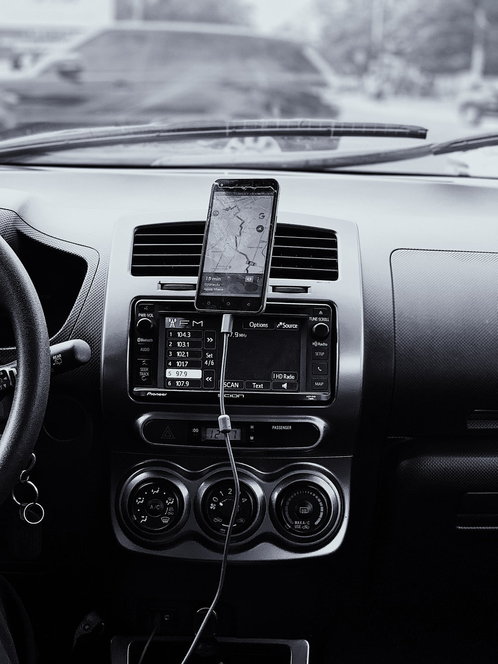 black car stereo turned on in grayscale photography
