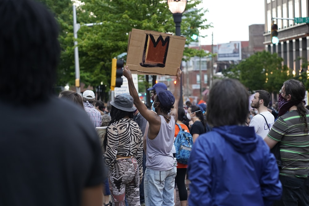 people standing and holding brown wooden board during daytime