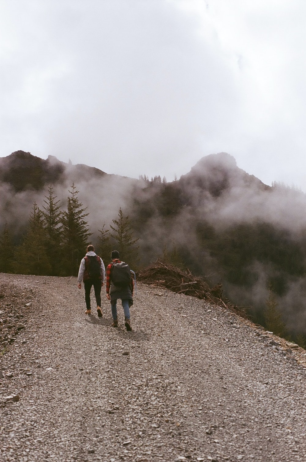 3 people walking on dirt road near foggy mountain during daytime