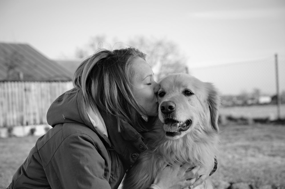 grayscale photo of woman kissing golden retriever