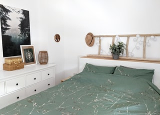 brown wooden cabinet beside green bed