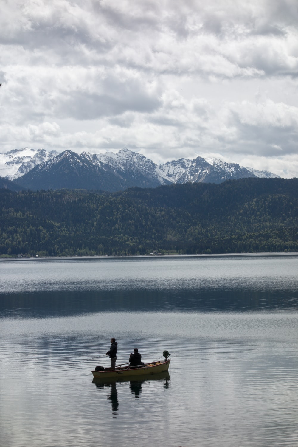 2 person sitting on rock near body of water during daytime