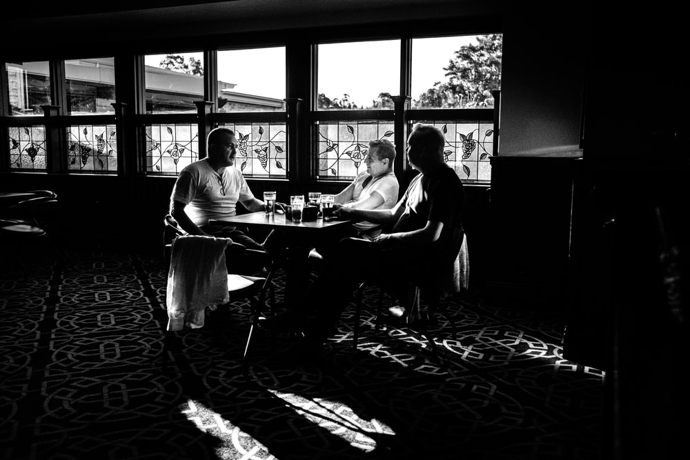 2 men sitting on chair in grayscale photography