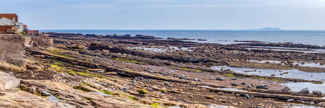 The rocky shores of Anstruther East Neuk of Fife, Scotland, low tide, with the Isle of May in the distance.