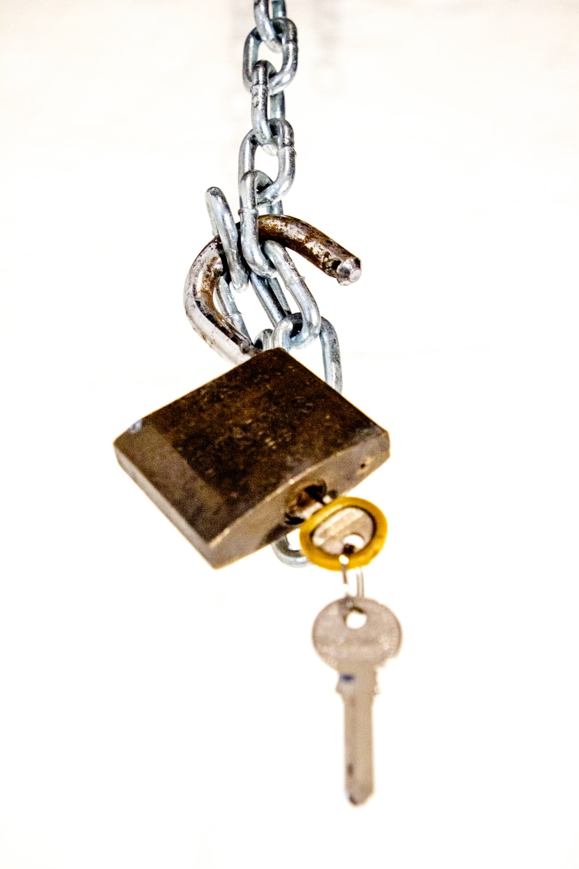 brass padlock with key on white background