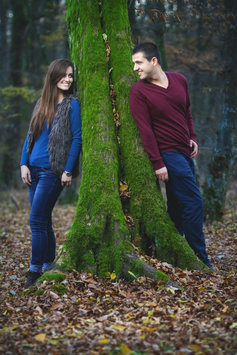 woman in maroon long sleeve shirt and blue denim jeans standing beside green moss covered tree