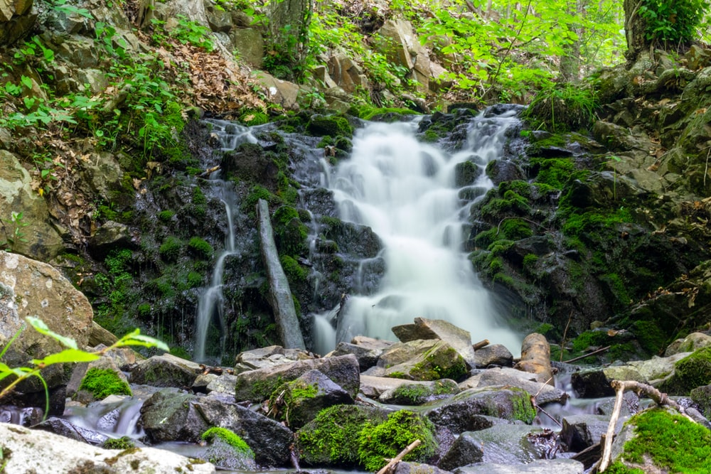 water falls on rocky shore during daytime