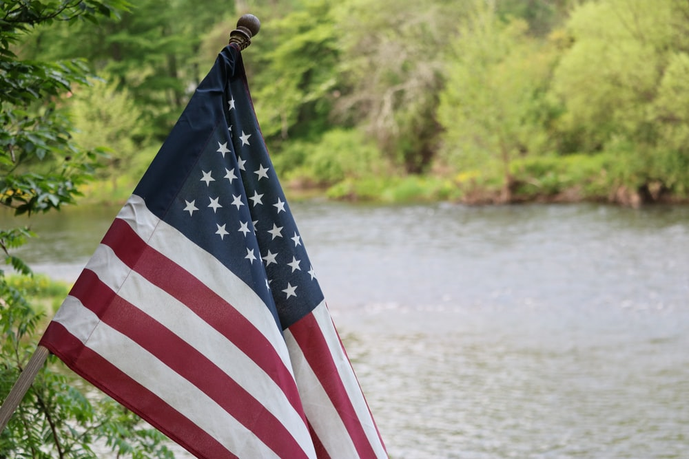 us a flag on pole near body of water during daytime
