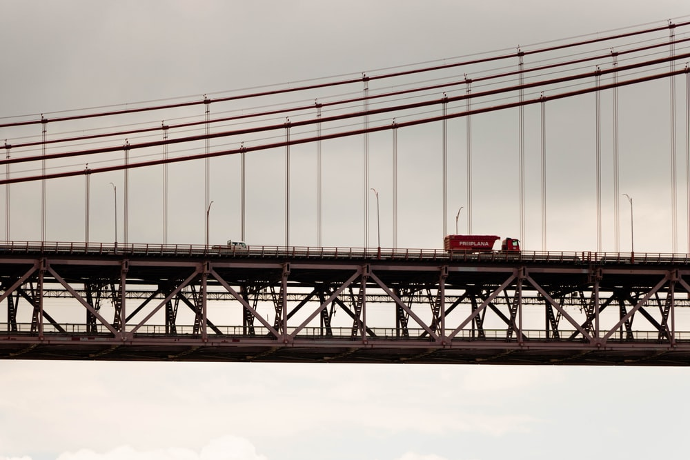 red and white train on bridge during daytime