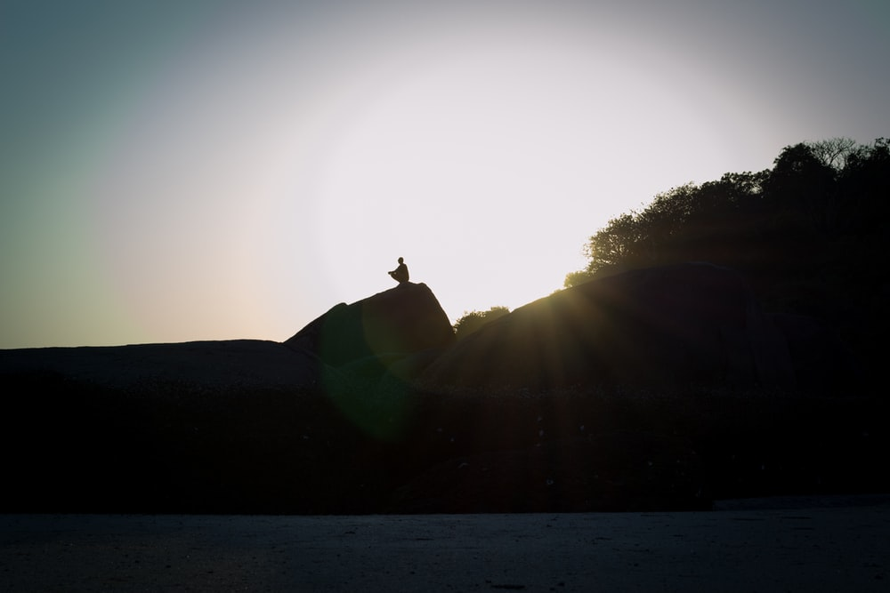 silhouette of man standing on hill during daytime