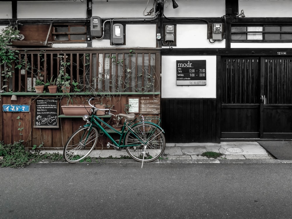 blue and green bicycle parked beside brown wooden house during daytime