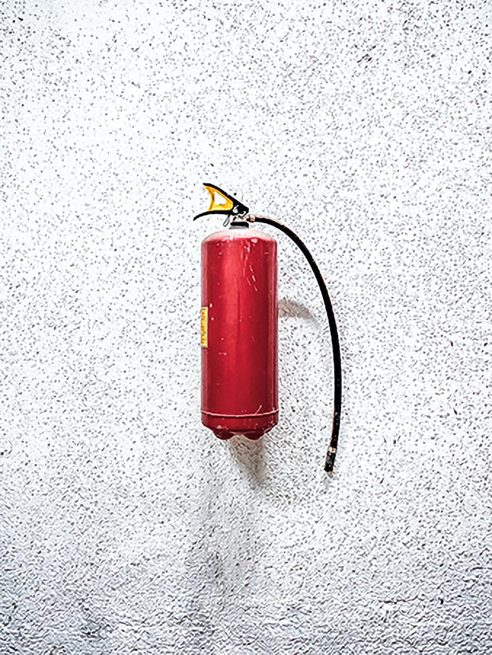 red fire extinguisher on white wall