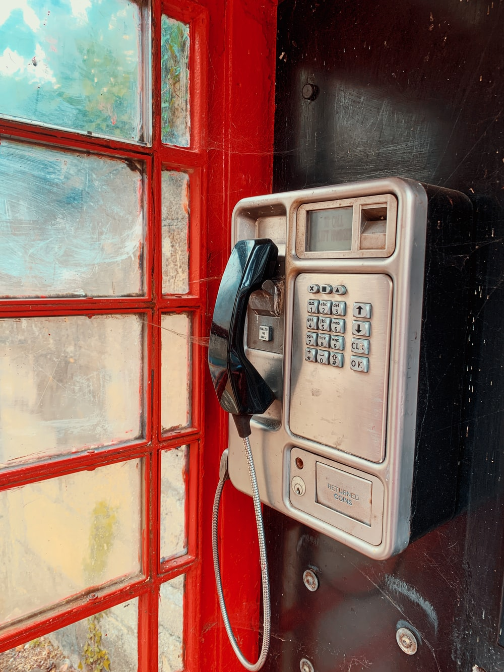 black and silver telephone on red and blue wooden wall