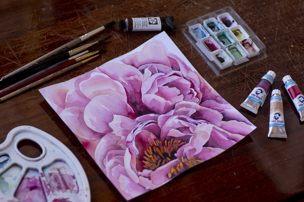 pink rose flower beside white and black soft tube