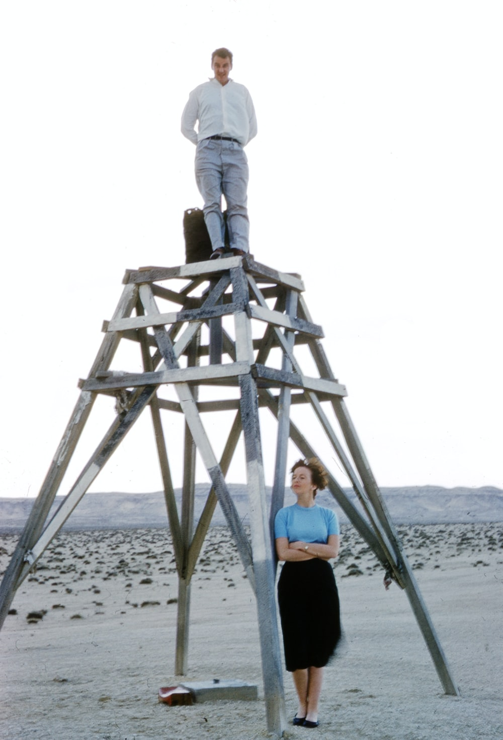 woman in blue shirt and gray pants standing on brown wooden ladder on beach during daytime