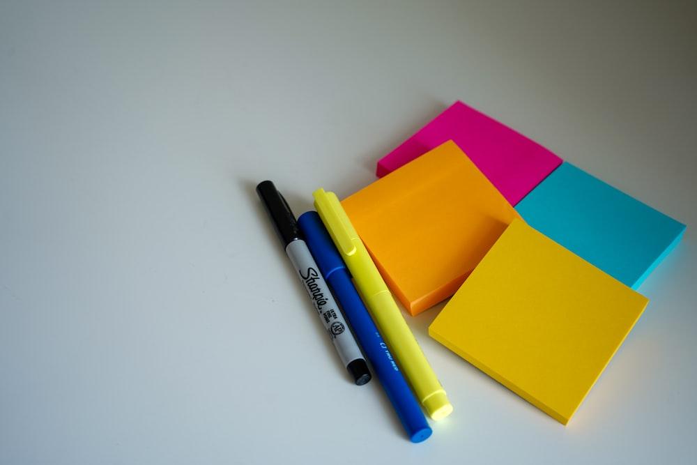 blue and black pen beside orange sticky notes