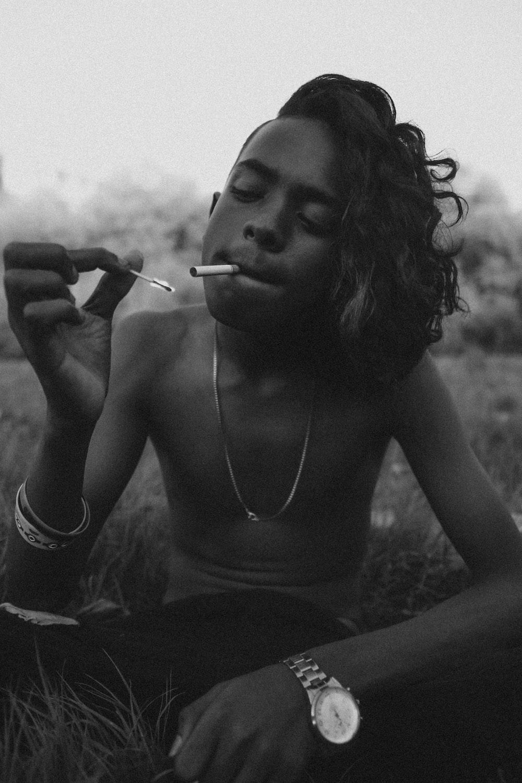 grayscale photo of woman smoking cigarette