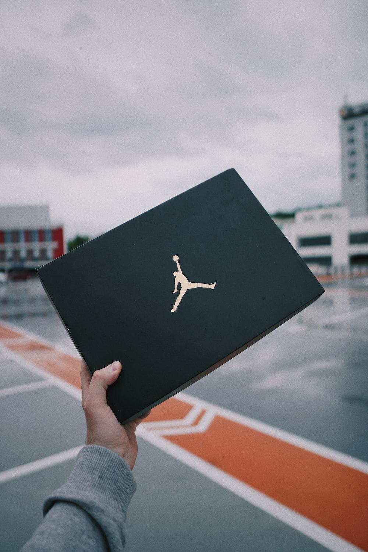 person holding black and white air jordan shoe box