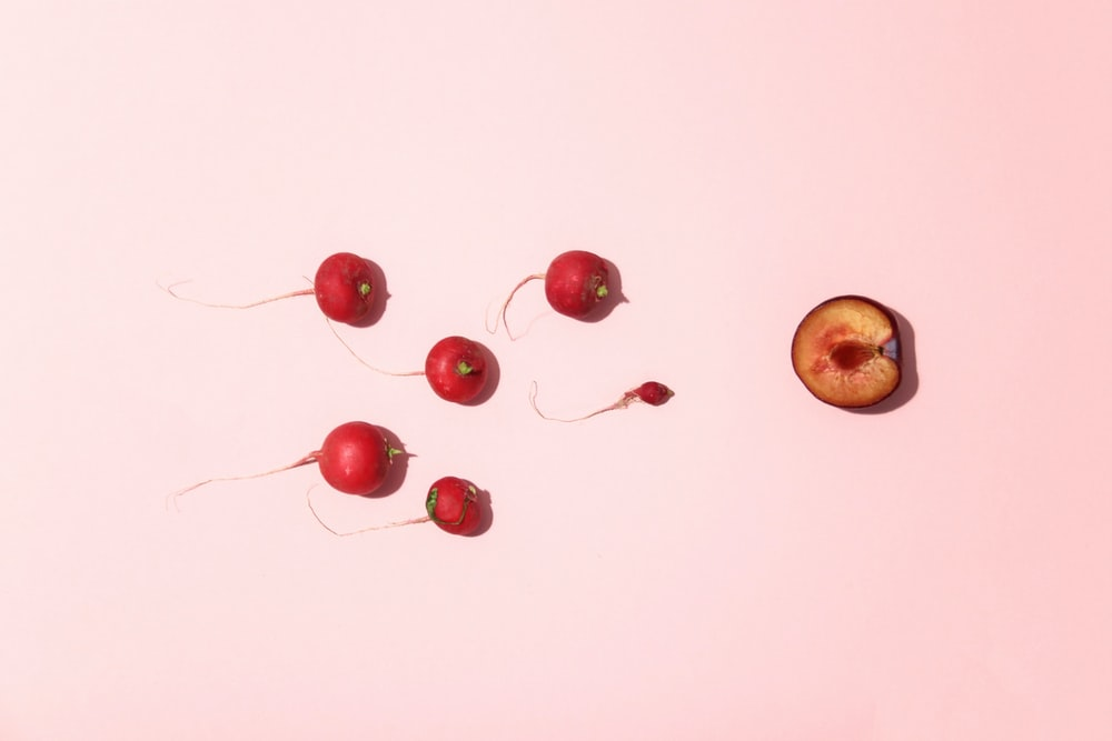 red cherry fruits on white surface