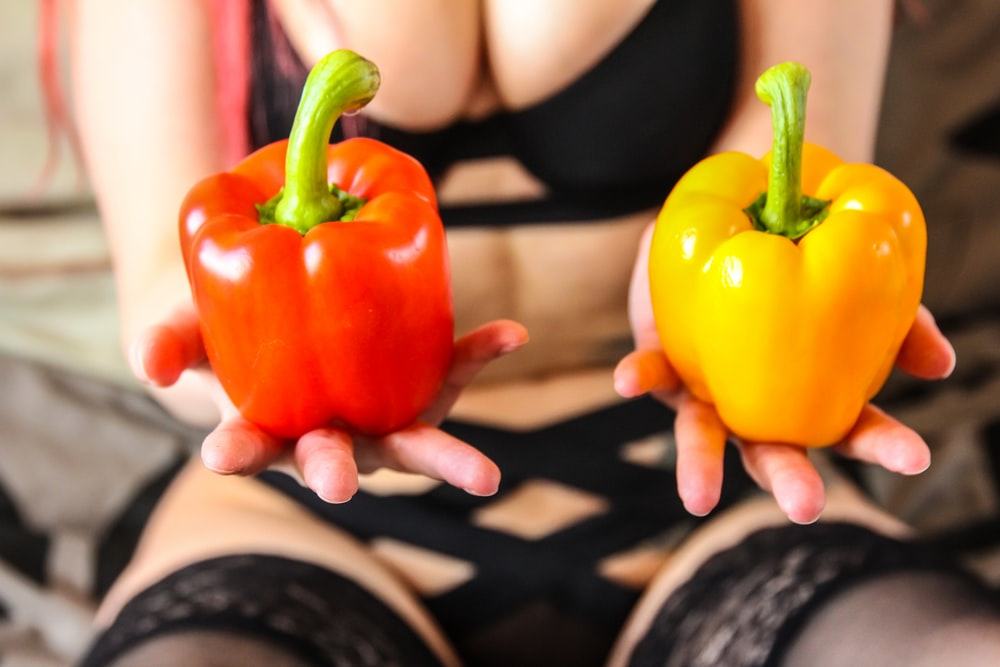 person holding yellow bell pepper