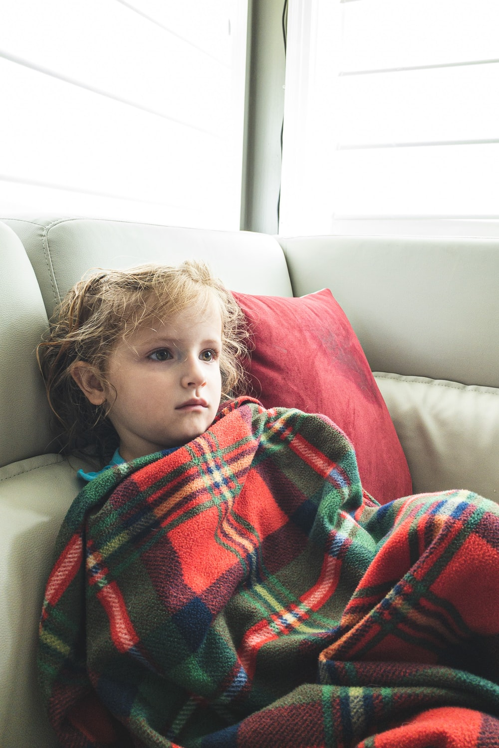 girl covered with red and black plaid blanket