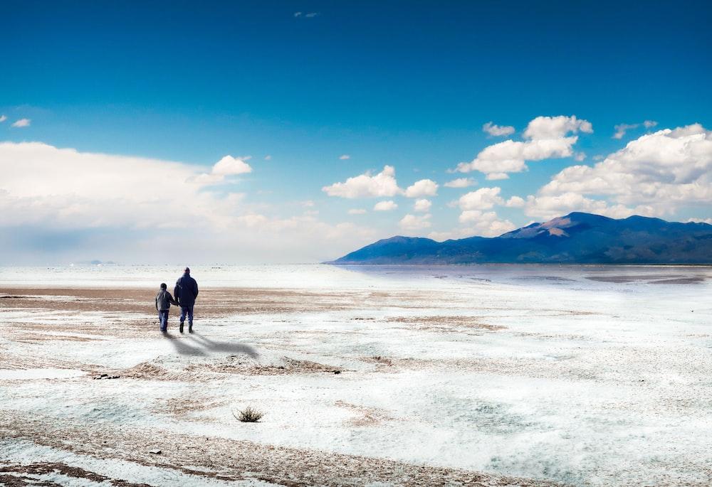 man in black jacket walking on white sand during daytime