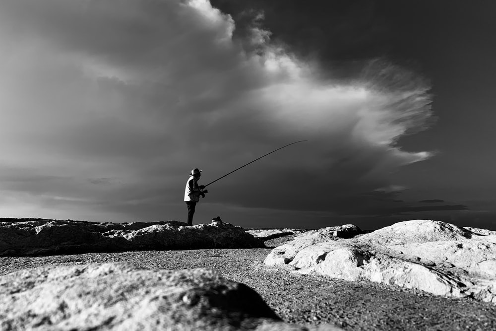 grayscale photo of man in black jacket and pants holding fishing rod
