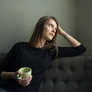 woman in black crew neck t-shirt holding green ceramic mug sitting on black sofa