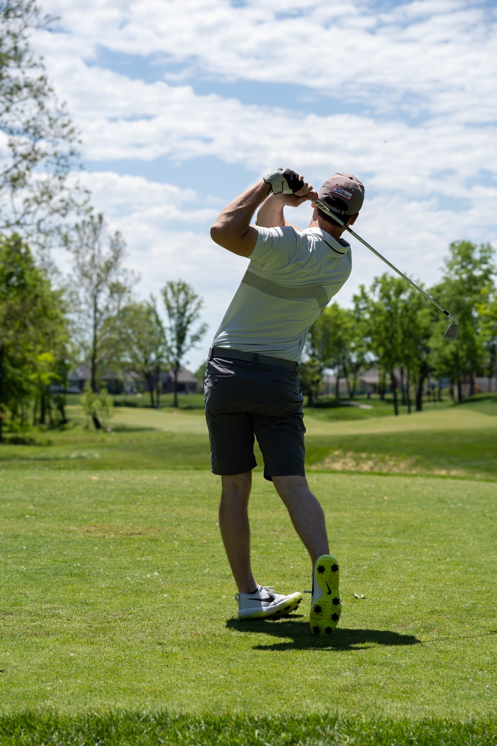 man in white t-shirt and black shorts holding golf club