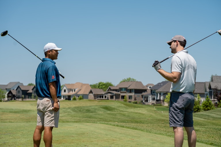 man in blue t-shirt and gray shorts playing golf during daytime