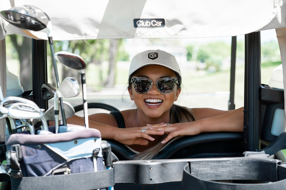 woman in black tank top wearing white sunglasses and white cap riding on black convertible car