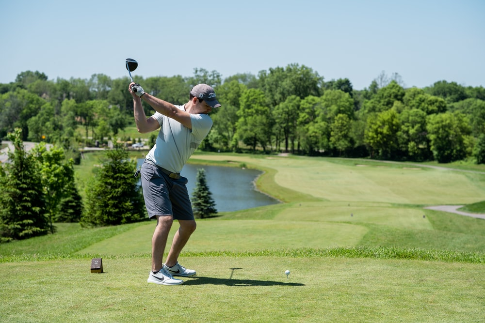 man in white t-shirt and black shorts playing golf during daytime
