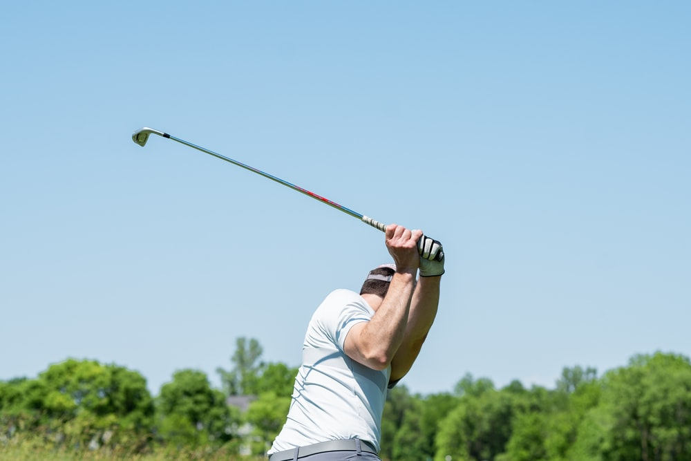 man in white tank top and white shorts playing golf during daytime