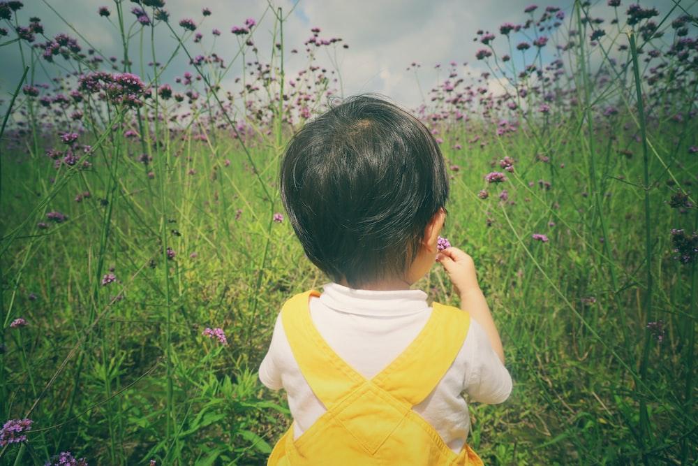 girl in yellow shirt standing on green grass field
