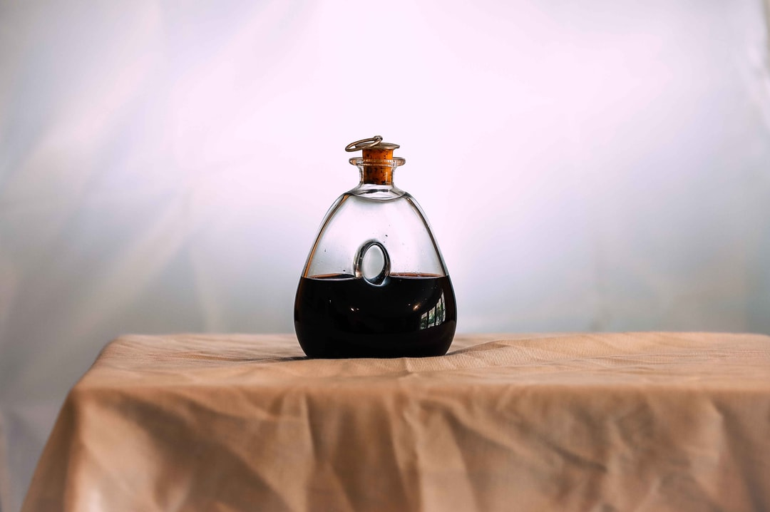Still life of a wine decanter on a white table with a white background.