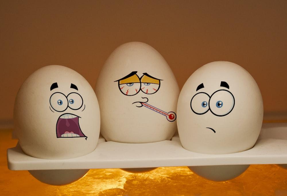 2 white and black ceramic egg figurines