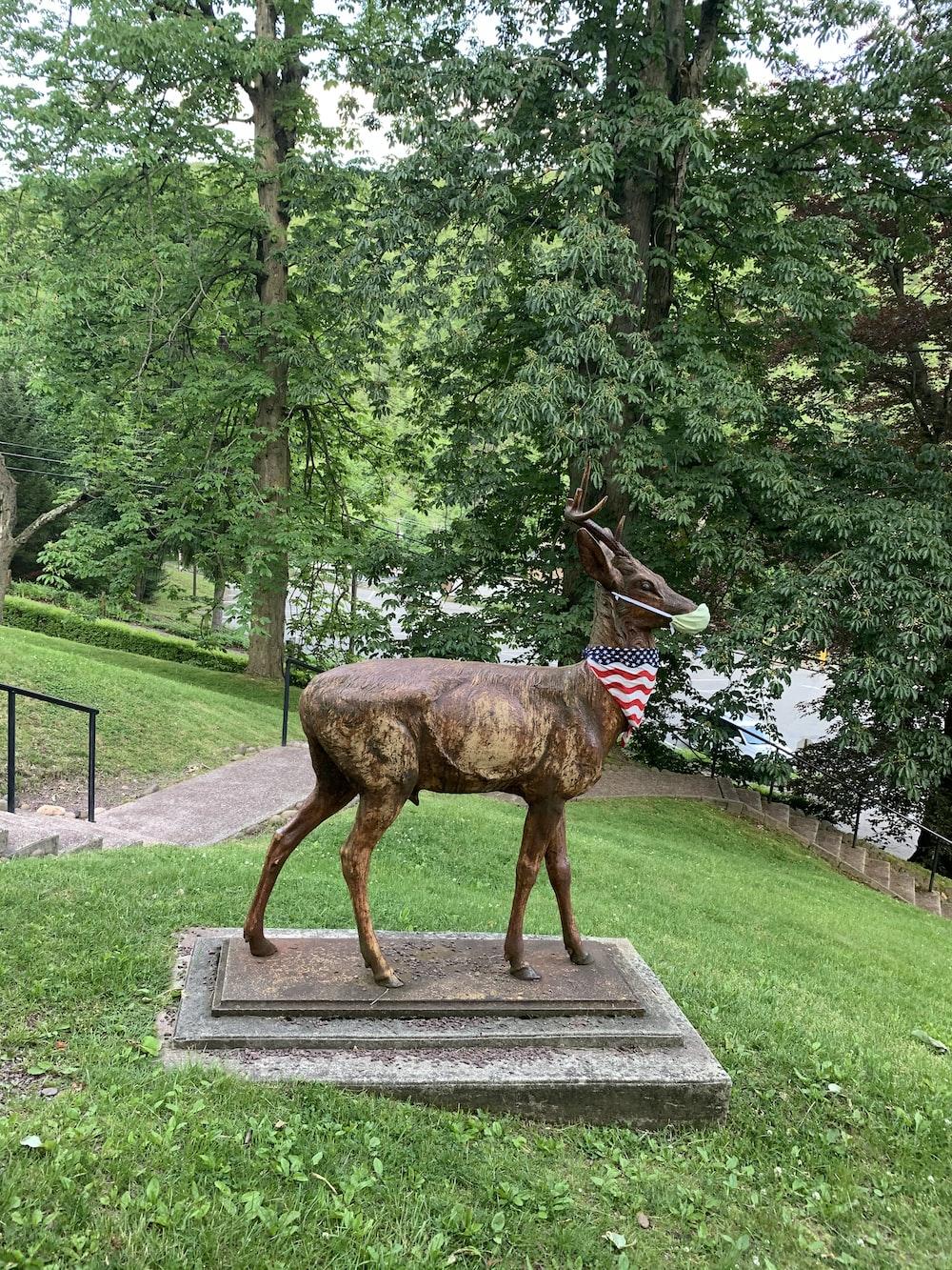 brown deer statue on gray concrete pathway