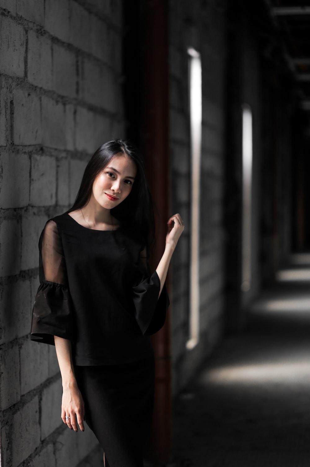 woman in black tank top standing beside wall