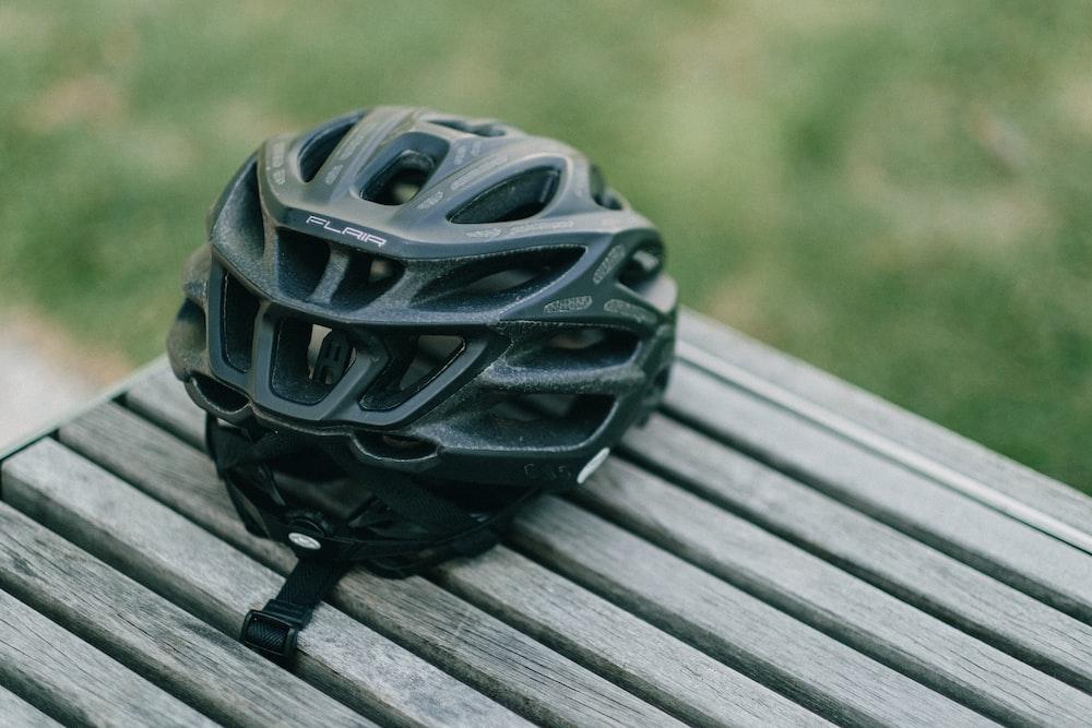 black plastic ball on gray wooden plank
