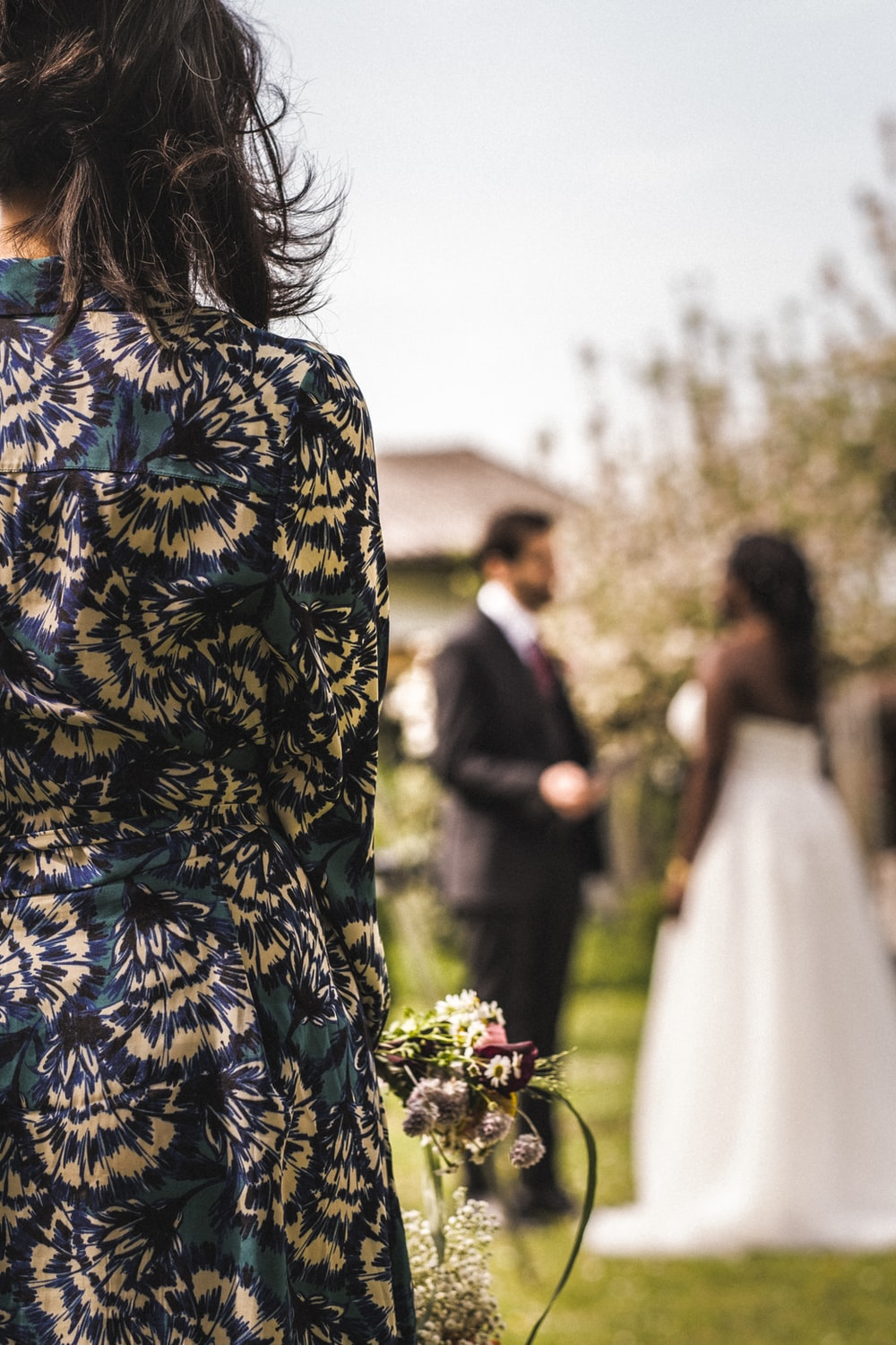 woman in blue and yellow floral dress standing beside man in black suit