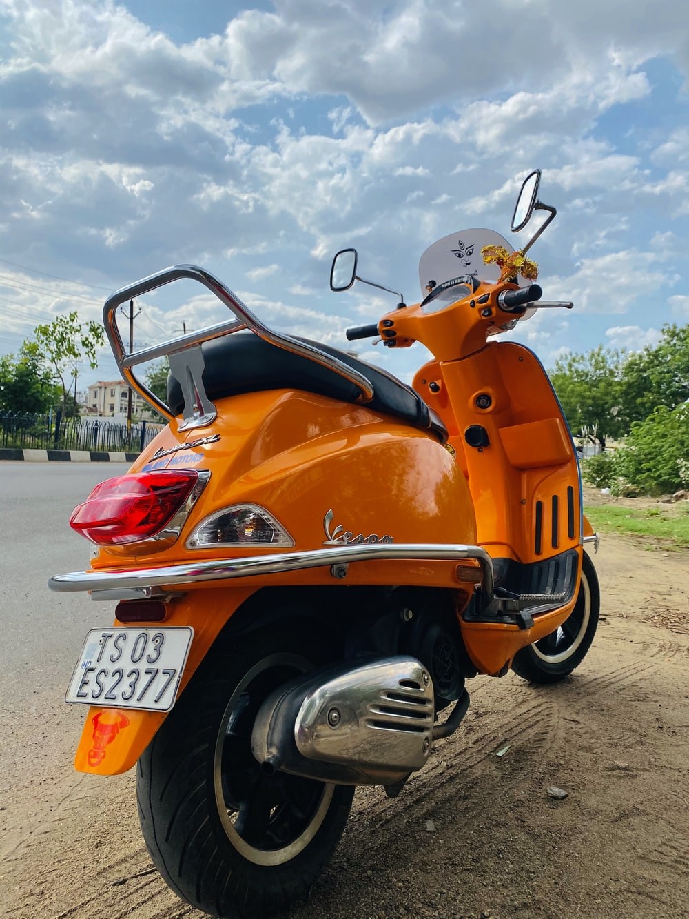 orange and black motor scooter parked on gray concrete pavement during daytime