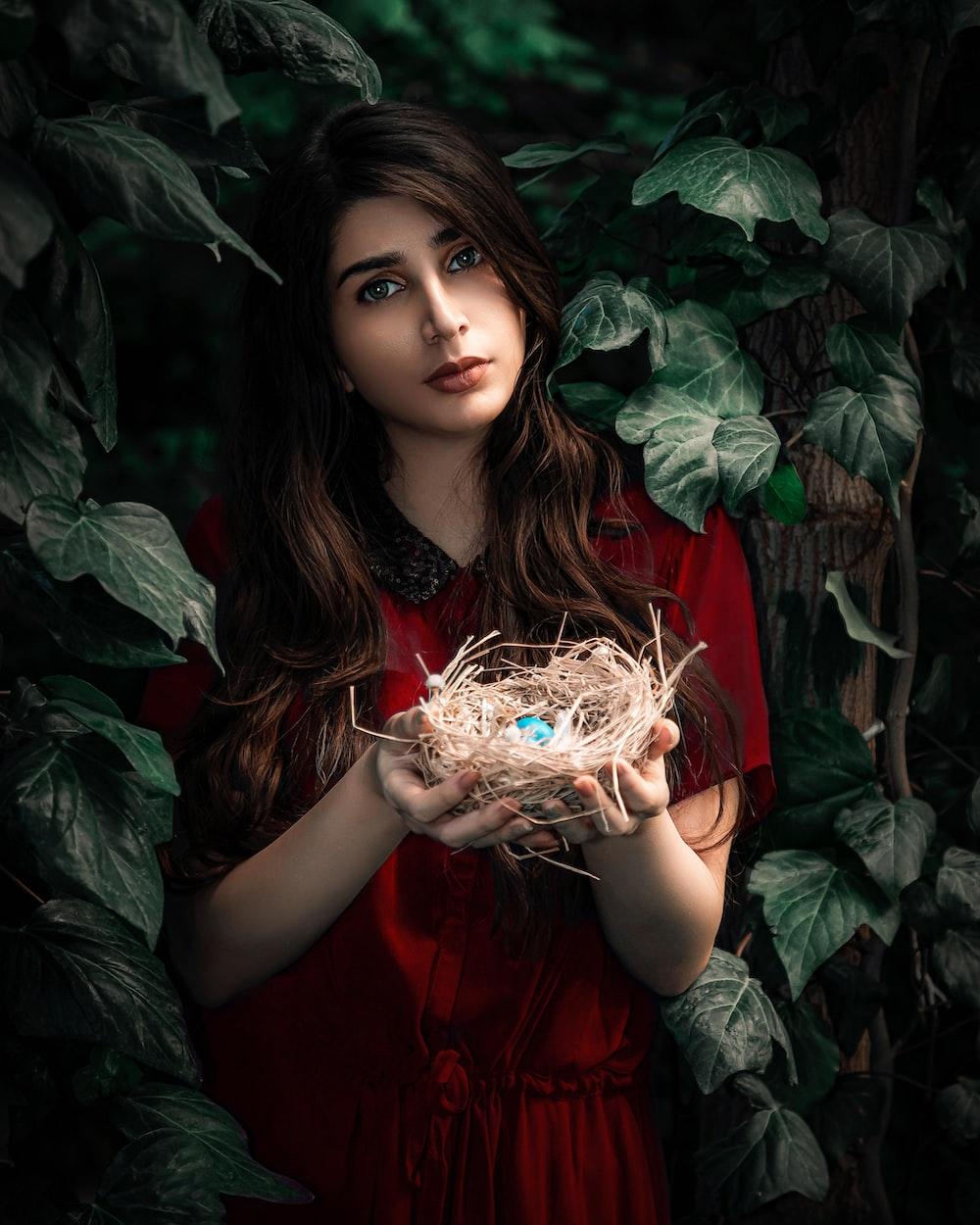 girl in red dress holding white flower