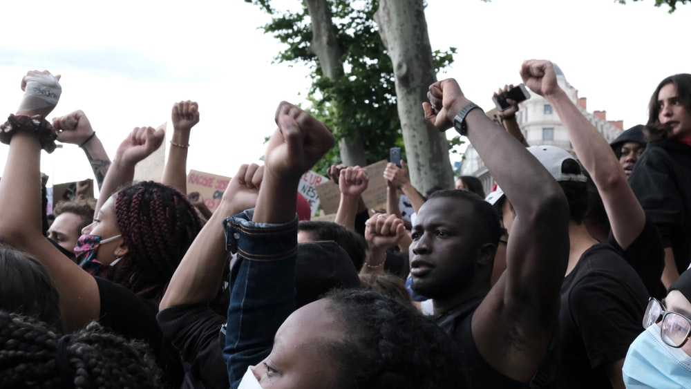 people raising their hands during daytime