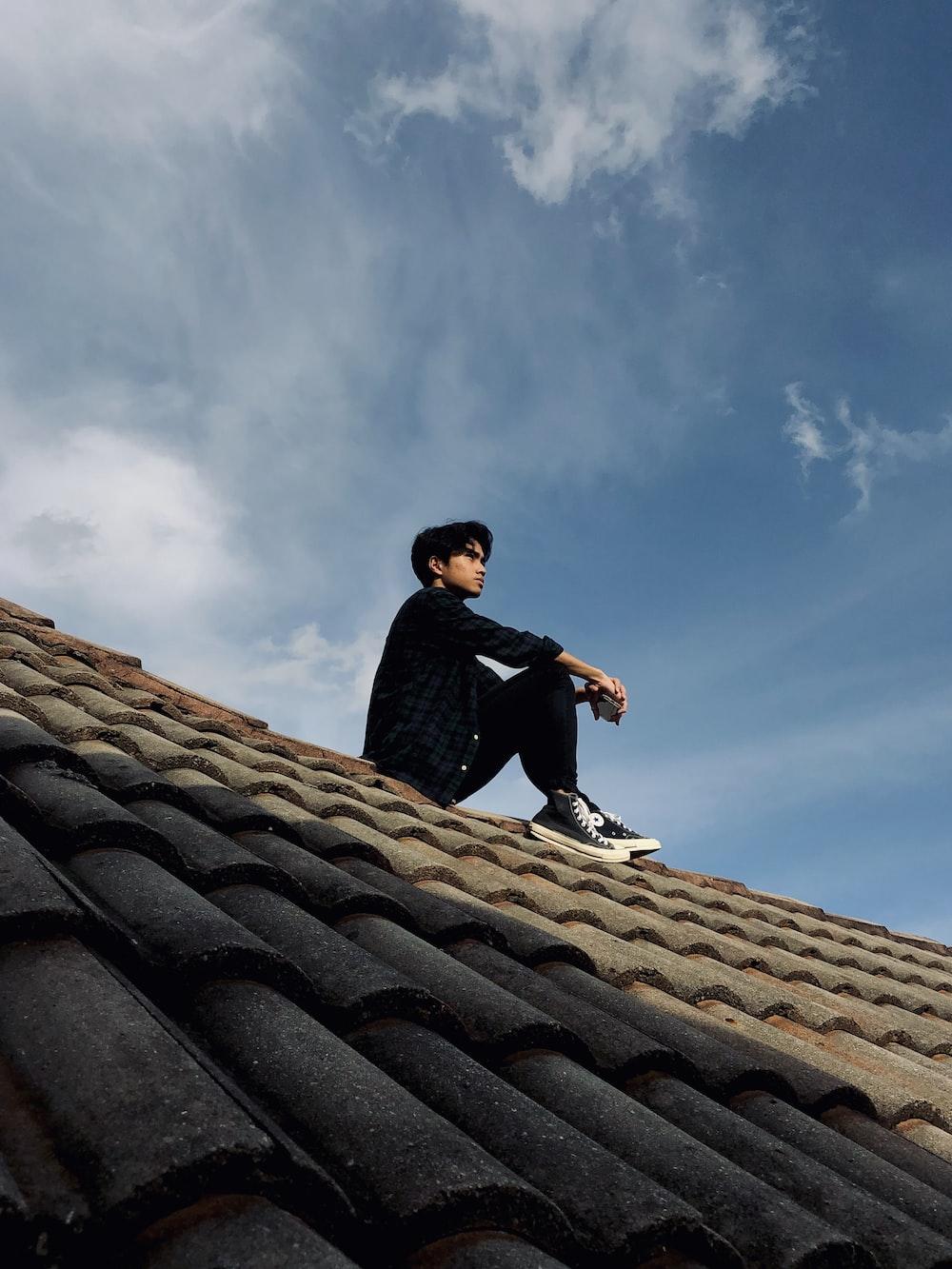 man in black jacket sitting on roof under blue sky during daytime